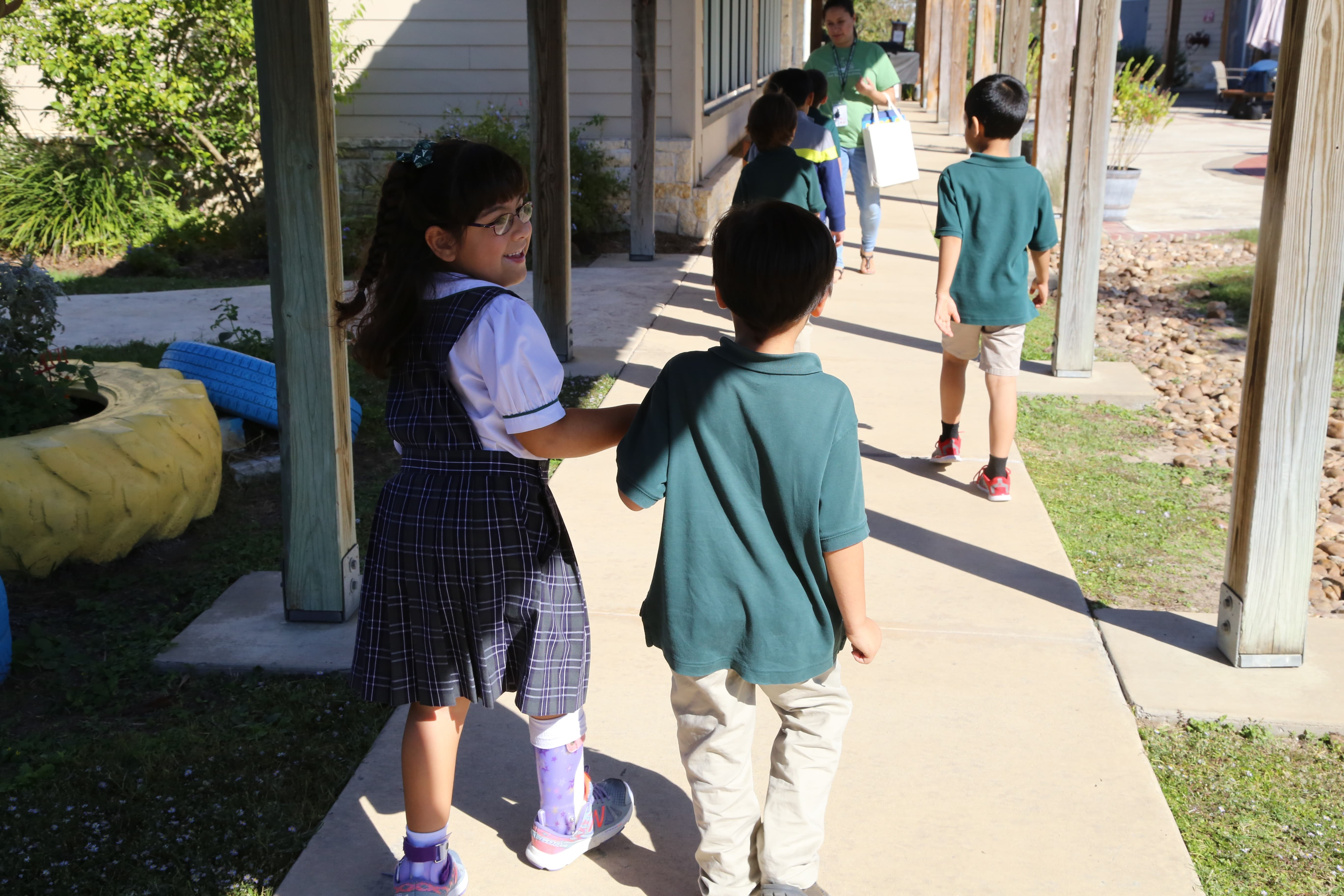 Students at The Parish School walk down the sidewalk holding hands