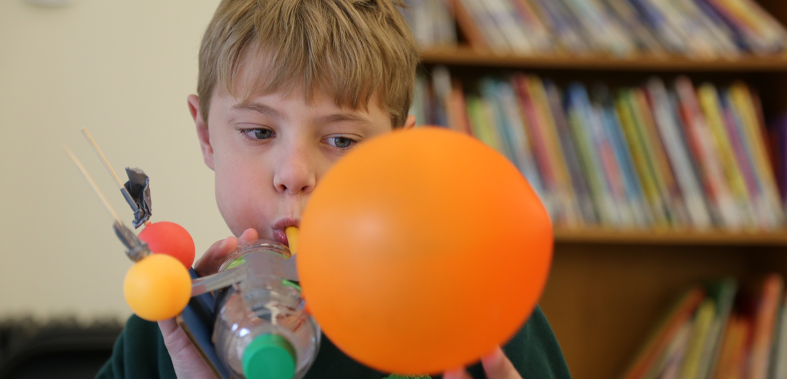 child blowing up balloon for balloon powered rocket in school makerspace