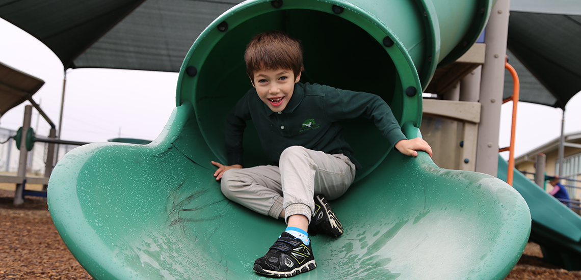 Student plays on slide at The Parish School