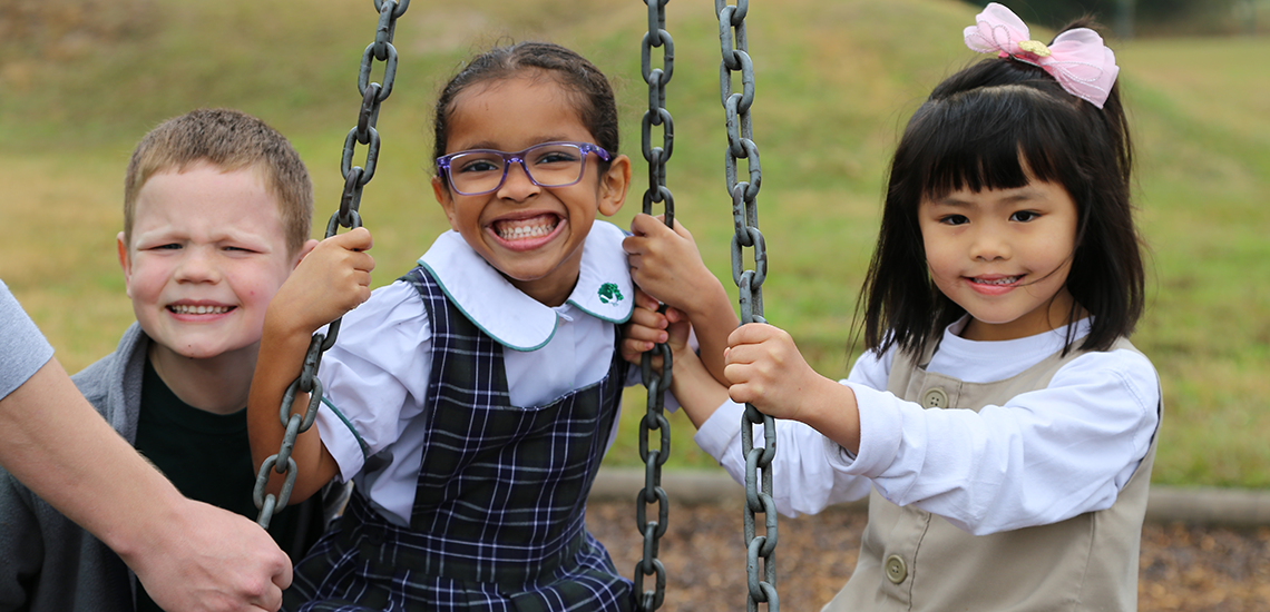 Elementary students playing together on swing at recess at The Parish School