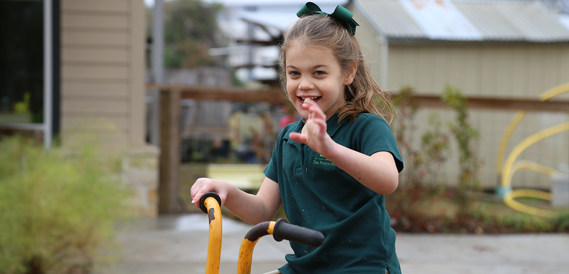 Early Childhood student rides bike during recess at The Parish School