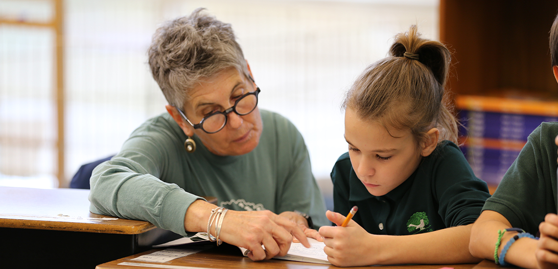 An elementary teacher/speech-language pathologist assists a student with assignment at The Parish School